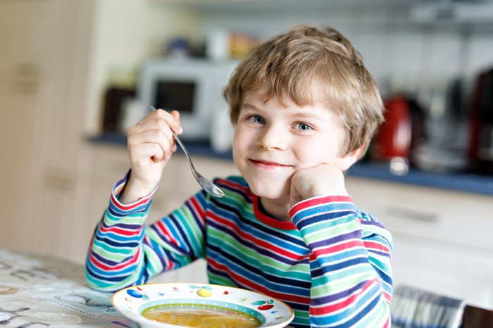 A boy, seated at a table in a striped, multicolored shirt, eating soup out of a bowl
