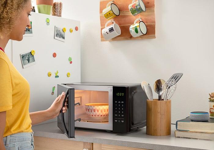 Woman heating bowl in microwave