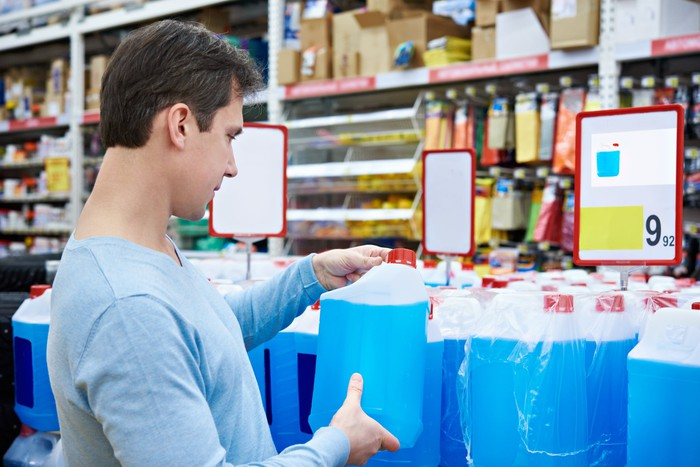 Man in an auto supply store examining a large bottle filled with blue fluid