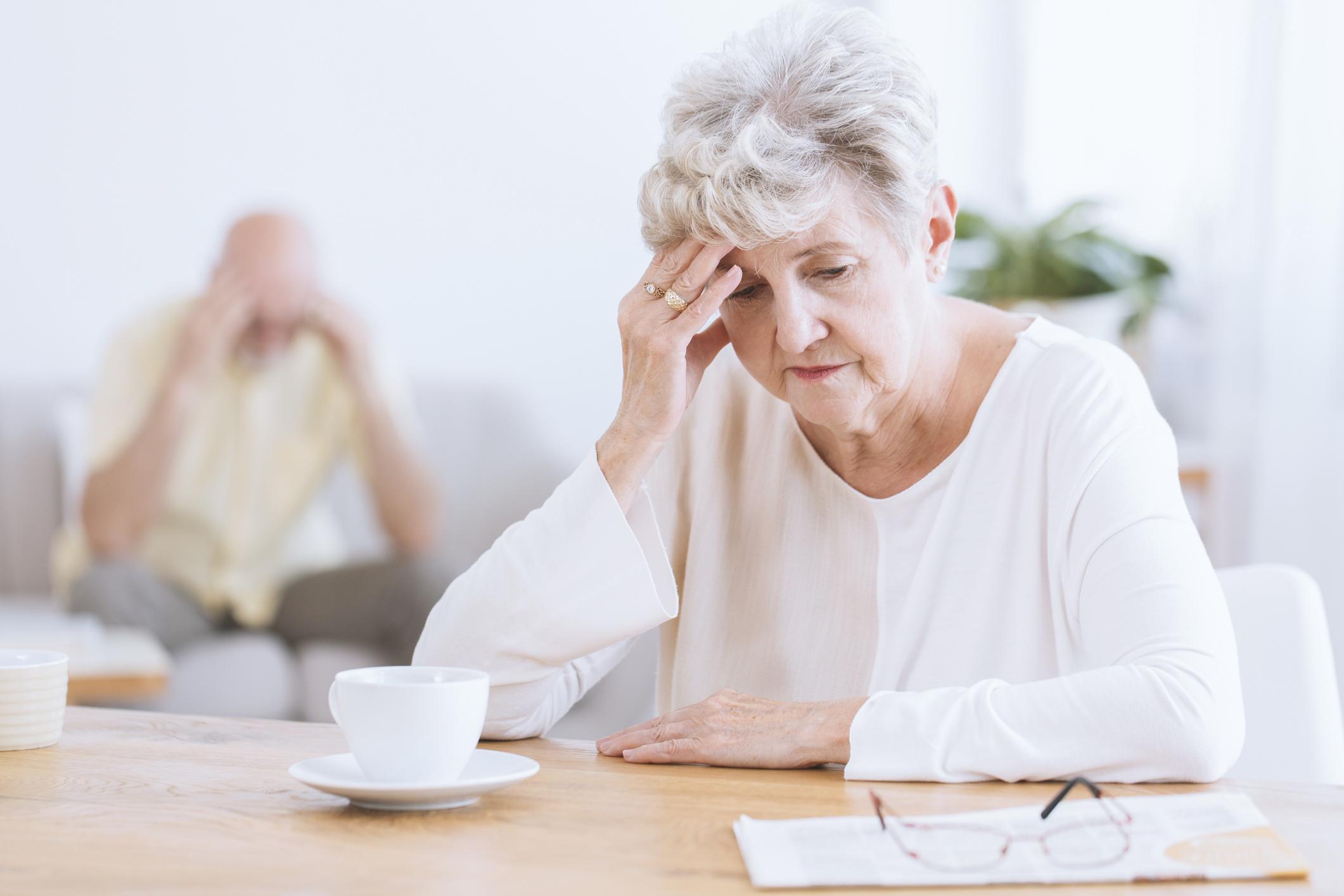Sad senior woman sitting at desk.