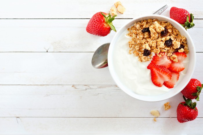 Yogurt with granola and strawberries in a bowl.