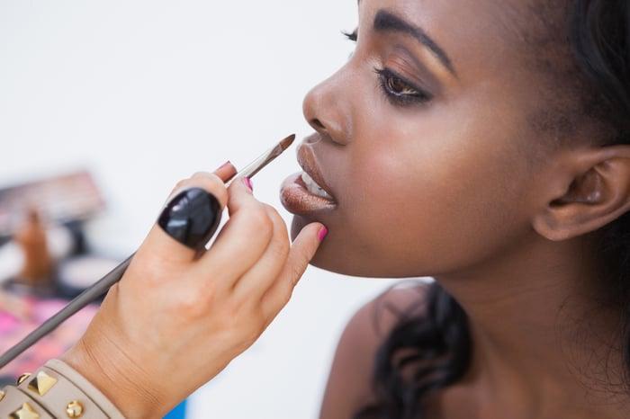 A makeup artist putting lipstick on a model.