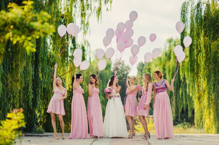 A bride with six bridesmaids in pink dresses, with more than 25 pink balloons.