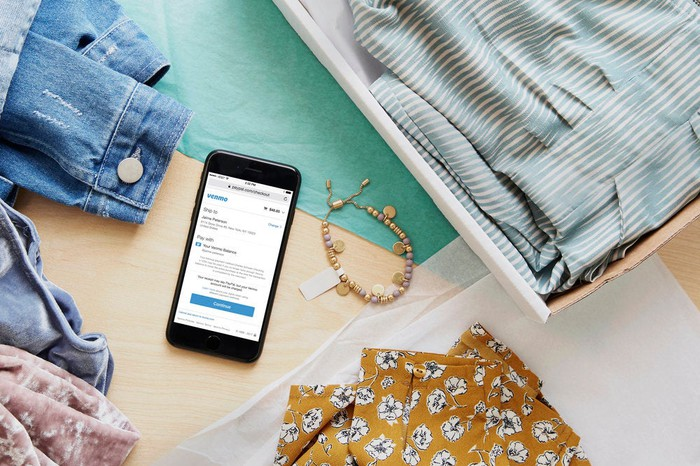 A phone with Venmo sitting on a table full of clothes for sale.