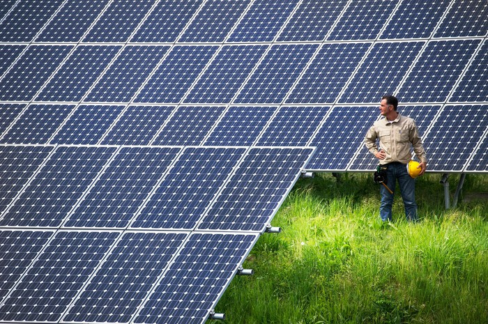 Worker at solar farm looking at solar panels while holding a yellow hard hat.