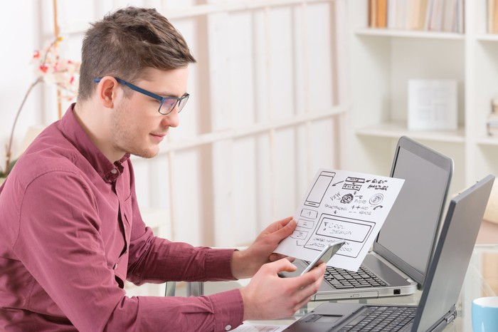 A man sits at a laptop holding a piece of paper detailing plans.