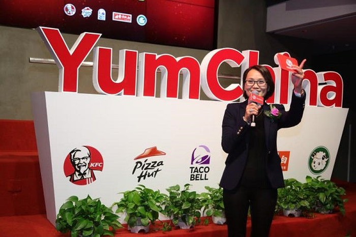 Yum China CEO Joey Wat speaking in front of a company sign with the KFC, Pizza Hut, and Taco Bell logos displayed.