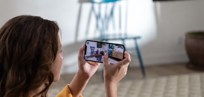 A woman uses an iPhone XS.