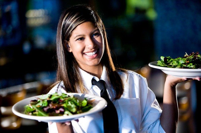 A waitress carrying salads in bowls.