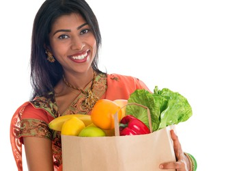 Indian Woman smiling carrying bag of groceries
