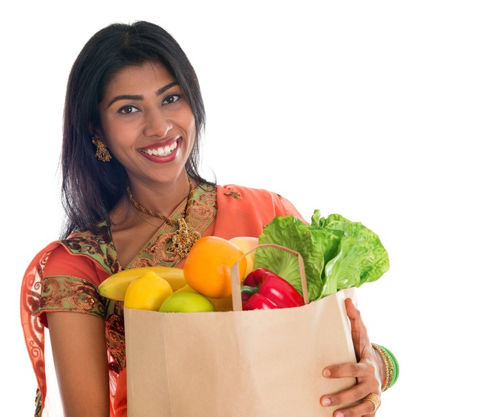 Indian woman smiling carrying bag of groceries.