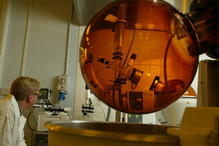 Laboratory with person in white lab coat looking at an amber-colored sphere with other equipment nearby.