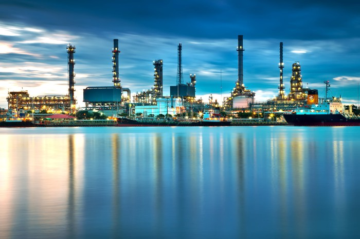 Oil refining facility on a body of water, in front of a mostly cloudy sky near dawn or dusk.