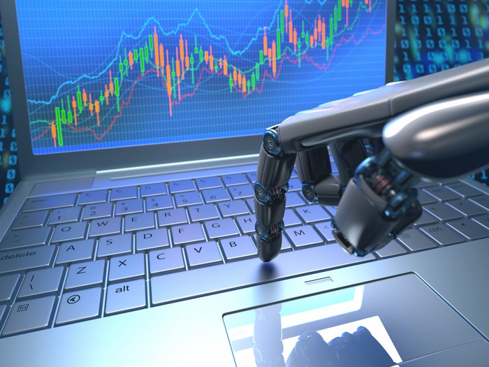 A robotic hand using a laptop to trade, with a rising stock chart on the laptop's monitor.