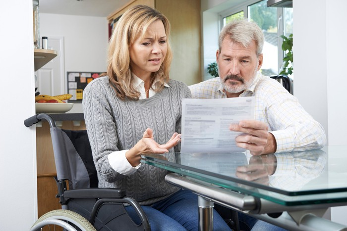 A woman in a wheelchair and a man look at a paper the man is holding.