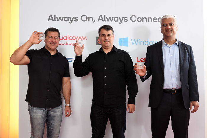 Three individuals holding Qualcomm chips.