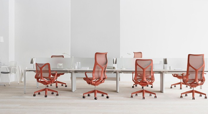 Red chairs surrounding a white desk.