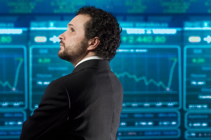 An investor in a suit, looking at various digital charts on a large ticker board.