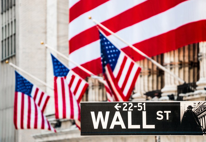 The facade of the New York Stock Exchange, flanked by American flags and the Wall St. street sign.