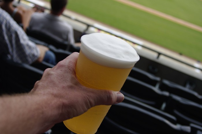 Man holding cup of beer a ballpark