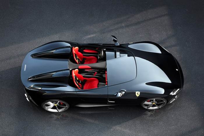 A black Ferrari Monza SP2, a sleek open-top sports car, viewed from above with its red seats visible.