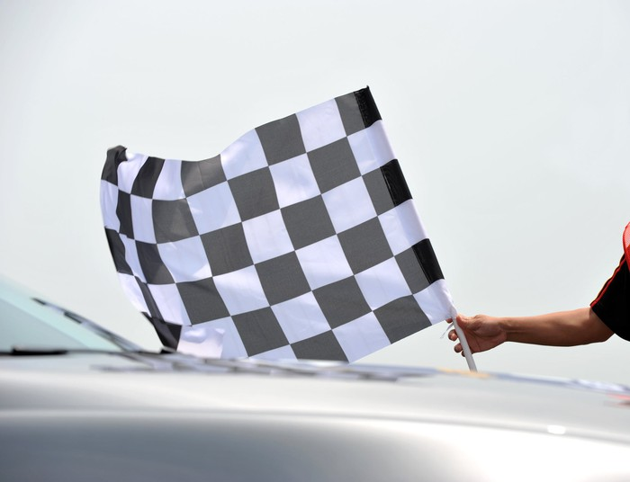 A person holding a checkered flag near a car.