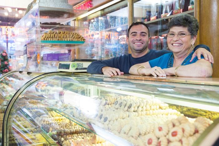 A youmger man has his arm around an older woman at the counter of a bakery.