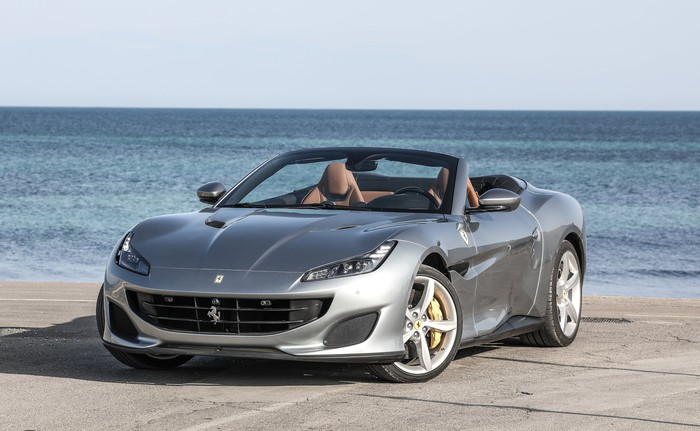 A silver Ferrari Portofino, a convertible, with its top down, parked on a waterfront.