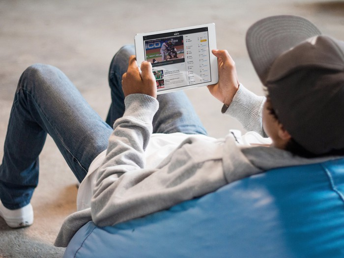 A young man with a ball cap sitting on a beanbag chair watching ESPN on an iPad.