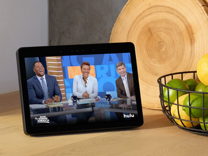 Echo Show on a counter next to a wire bowl holding lemons and limes