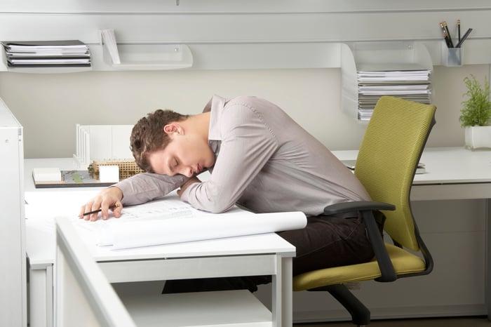 Man sleeping at desk.