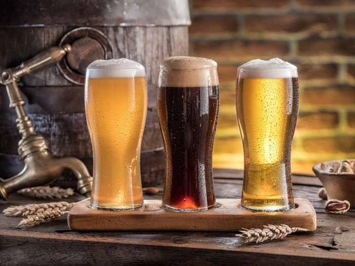 Three beers placed on a bar top.