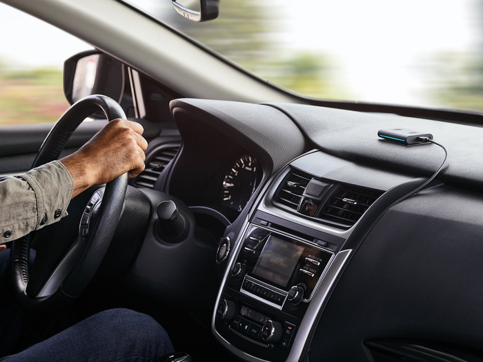 A view of the front dash in a vehicle, with a man's arm seen on the steering wheel