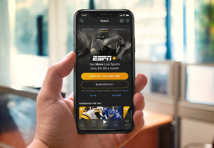 A person holds up a phone showing ESPN+