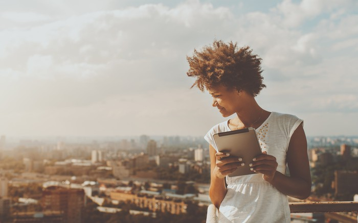 Woman standing with a tablet, overlooking a city