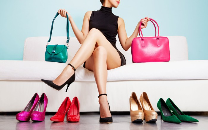 Woman sitting on couch amidst handbags and shoes.
