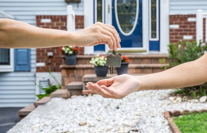 Person handing over house keys to another, with a house in the background