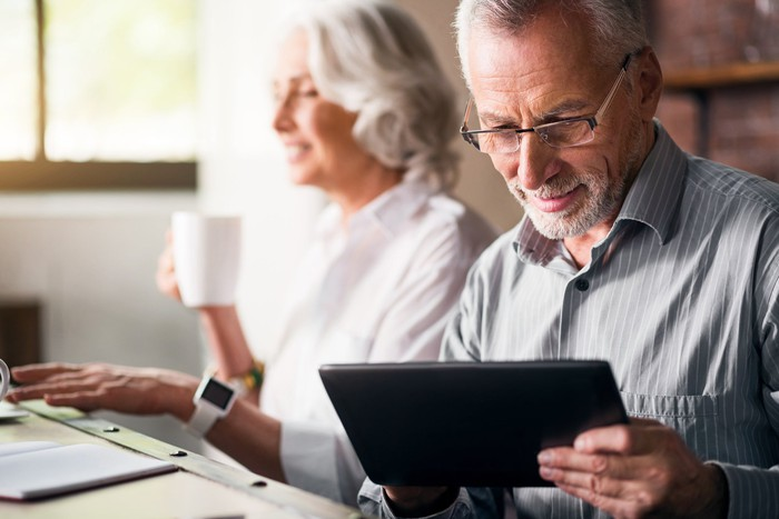 An older couple sitting at a table using their electronic devices while drinking coffee.