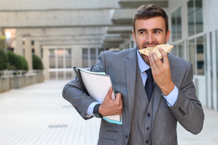 Man in a business suit carrying two binders under his arm and eating a sandwich on the go