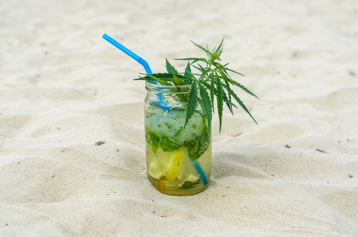 A drink in the sand with a marijuana leaf in it.