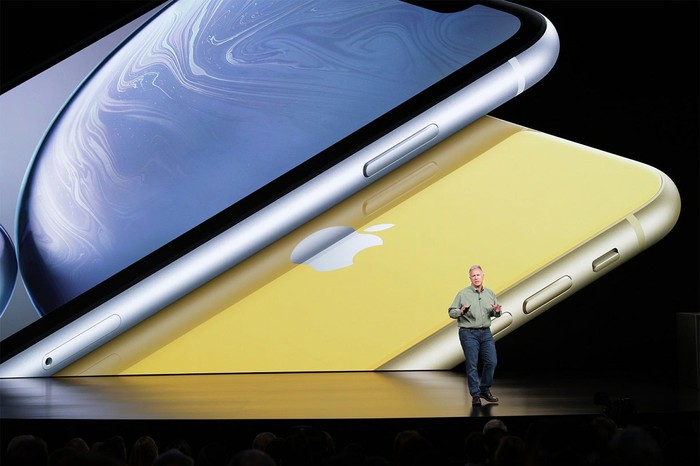 Apple marketing chief Phil Schiller on stage with an image of two iPhone XR phones behind him.