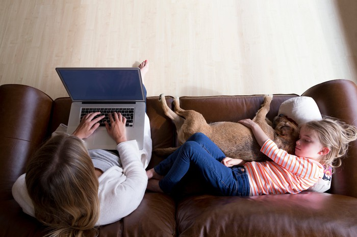 A woman types on a laptop next to a child cuddling a dog.