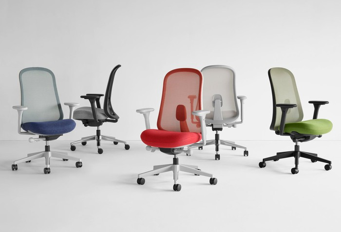 "A group of colorful Herman Miller ""Lino"" chairs arranged on a white background."