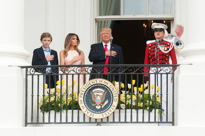 President Trump with his right hand over his heart during the singing of the national anthem, flanked by his wife Melania, and his son Barron.