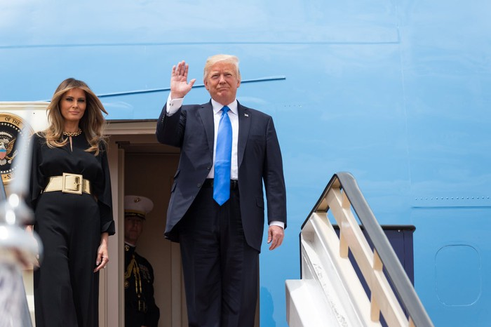President Trump waving to reporters before entering Air Force One, with First Lady Melanie Trump by his side.