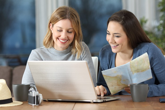Two women look at a map and a computer