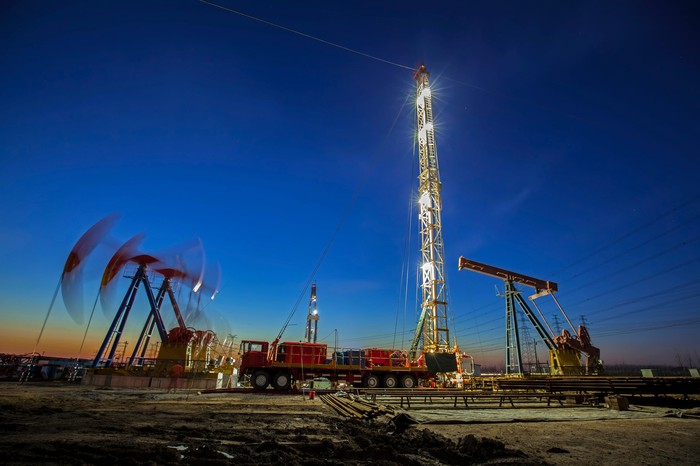 Oil pumps working the the background near a drilling rig.