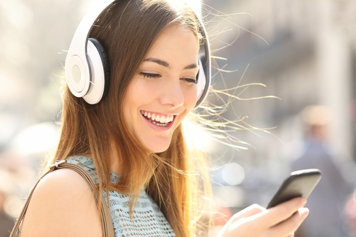 A woman wearing wireless headphones is holding a smartphone.