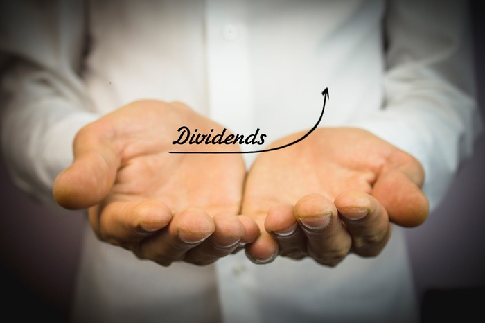 Man holding out his hands with the word Dividend written above it with an arrow indicating growth