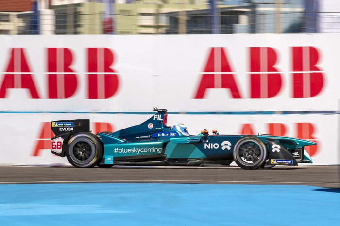 A NIO Formula E single-seat electric race car, shown at speed on a track.
